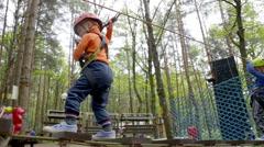 Little boy in helmet walks by pendant path - stock footage
