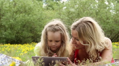 Beautiful woman and girl playing on a tablet, in the nature Stock Footage