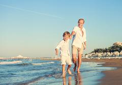 Little son and father runs together on sea surfline Stock Photos
