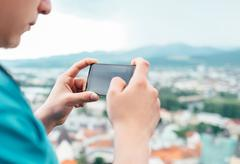 Close up image man hands with modern phone taking picture of city landscape Kuvituskuvat