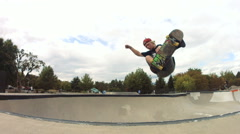 Skateboarder doing a frontside indy grab Stock Footage