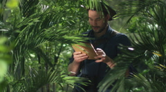 Adventurer in Hat using Tablet in Jungle Forest. Stock Footage
