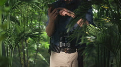 Adventurer in Hat using Mobile Phone in Jungle Forest. - stock footage