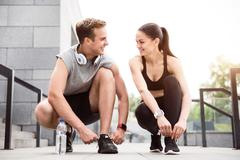 Couple squatting and tying their shoelaces Stock Photos