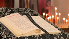 The Bible in expanded form, against the Church of candles - stock footage