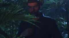 Adventurer in Hat Walking through Jungle Forest at Night Stock Footage