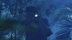 Adventurer in Hat Walking through Jungle Forest in Night. Using Flashlight Stock Footage