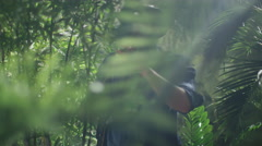 Adventurer in Hat Walking through Jungle Forest - stock footage