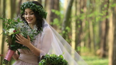 Beautiful young brunette bride in laurel wreath with big bouquet of white spring Stock Footage