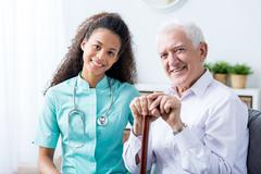 Afroamerican carer with stethoscope sitting next to senior man with walking stic - stock photo