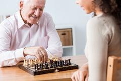 Happy senior man playing chess with young woman. - stock photo