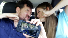Funny man and woman making crazy selfie in car Stock Footage