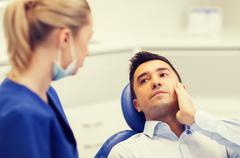 female dentist and male patient with toothache - stock photo
