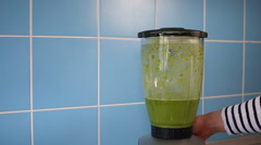 A blender jar with green healthy smoothie on blue - stock footage