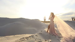 Young high-fashion dressed couple on the sandy beach on sunset Stock Footage