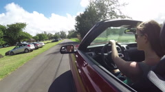 SLOW MOTION: Young woman in red convertible driving through Hawaii village Stock Footage