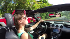 SLOW MOTION: Happy woman in red convertible driving through palm tree promenade Stock Footage
