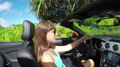 SLOW MOTION: Young woman in cabrio car driving pass exotic trees along the beach Stock Footage