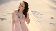 Gorgeous brunette woman in long pink dress posing dynamic in the beach. Waving Stock Footage