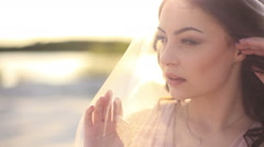 Sensual young brunette woman covering her face with a veil.  Close-up shot Stock Footage