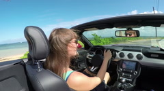 CLOSE UP: Happy woman with wind in her hair driving convertible along the beach - stock footage