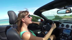 CLOSE UP: Young woman with wind in her hair driving convertible along the beach Stock Footage