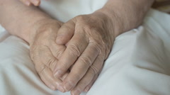 A young female hands comforting an elderly pair of hands of old women Stock Footage