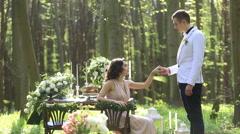 Wedding forest dinner. Handsome groom kisses hand of beautiful brunette bride Stock Footage