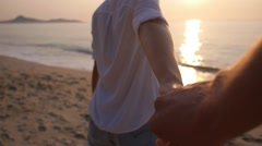 Woman Holding Hand of Boyfriend Following Her at Sea Sunset Stock Footage