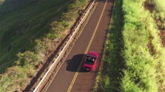 AERIAL: Red convertible driving on empty countryside road in sunny nature Stock Footage