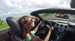 SLOW MOTION: Smiling woman driving on coastal road in luxury red convertible car - stock footage