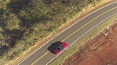 AERIAL CLOSE UP: Couple in red convertible car driving along countryside road - stock footage