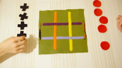 Two players placing cross and circle pieces over cloth 4K Stock Footage