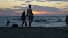 Family, enjoy the sunset from the beach on the island. Stock Footage