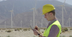 Technician using stylus with tablet computer at wind farm 4K Stock Footage