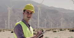 Wind farm technician looks up and checks time while making notes 4K - stock footage