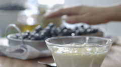 Blueberries being placed on natural homemade organic yogourt - stock footage