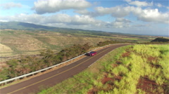 AERIAL: Luxury red convertible car driving along beautiful countryside in Hawaii - stock footage