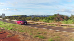 AERIAL: Red convertible car driving uphill along grand Waimea canyon landscape - stock footage