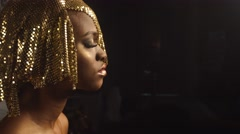 Side view of magic surreal golden african american female model with bright Stock Footage