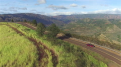 AERIAL: Red convertible driving on winding road on the edge of grand canyon - stock footage