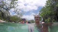 A couple floating down ancient Mayan canal Stock Footage