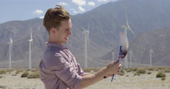 Young man smiling and giving thumbs up with pinwheel at wind farm 4K - stock footage