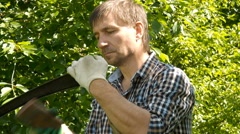 A male sharpening scythe tool with stone in in hot summer day Stock Footage