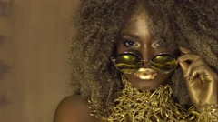 Magic surreal golden african american female model in massive sunglasses with - stock footage