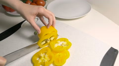 Woman slice yellow pepper at the cutting board - stock footage