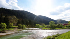 Rocky mountains and river with a rapids flowing in a valley between mountain Stock Footage