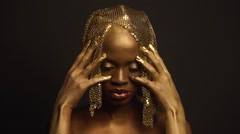 Enigmatic african american female model with golden glossy makeup and headwear Stock Footage
