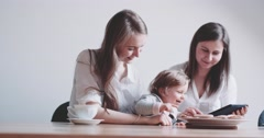 Two Women working on Laptop, holding baby girl. Slow Motion 4K DCi. Stock Footage
