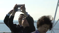 Tourists from China enthusiastically taking pictures of the seagulls - stock footage
